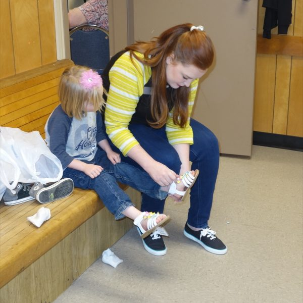 16 - A volunteer helps a little girl try on new shoes