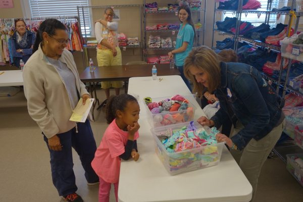 5 - Volunteers help a little girl pick out new clothes