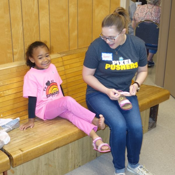 8 - A volunteer helps a girl try on shoes