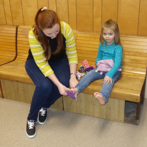 9 - A volunteer helps a little girl try on shoes