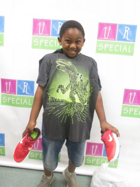 A boy shows off his shirt and shoes