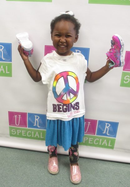 A girl proudly shows off her new shoes