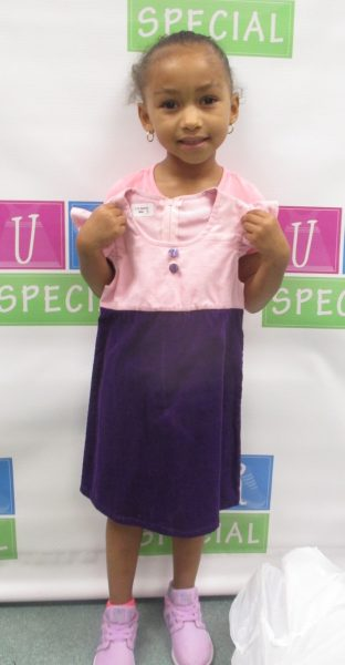 A young girl shows off her dress
