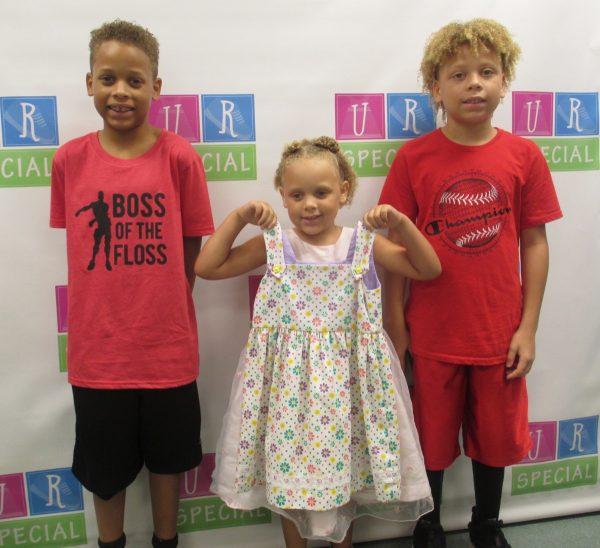Three children show off their clothes