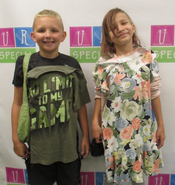 Two kids show off their clothes